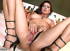 Stunning Sandy fingers her hot pussy lying on a sofa
